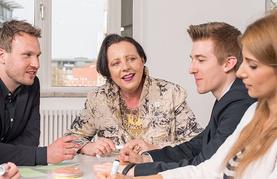 Personen sitzen um einen Tisch und sprechen miteinander