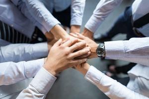 Hände verschiedener Personen, die übereinander liegen