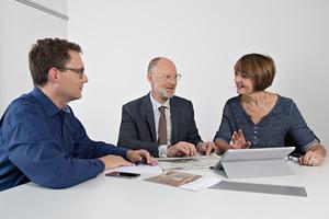 Drei Mitarbeiter sitzen an einem Tisch und besprechen sich