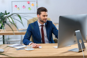 Angestellter sitzt vor Computerbildschirm
