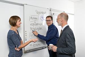 Mitarbeiter des Staatsanzeigers für Baden-Württemberg vor einem Whiteboard stehend und unterhaltend