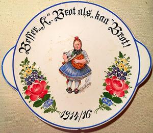 """""""Besser 'K' Brot als 'kaa' Brot! – 1914/16"""". Der Wandteller von 1916 spielt auf das Brot aus Kartoffelmehl an, das seit der ersten Kriegshungerkrise 1915/16 weit verbreitet war."""