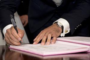 Hand, die ein Dokument unterschreibt