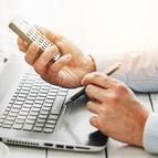 Person am Laptop mit einem Taschenrechner in der Hand