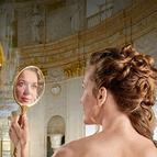 Frau betrachtet sich selbstverliebt im Spiegel