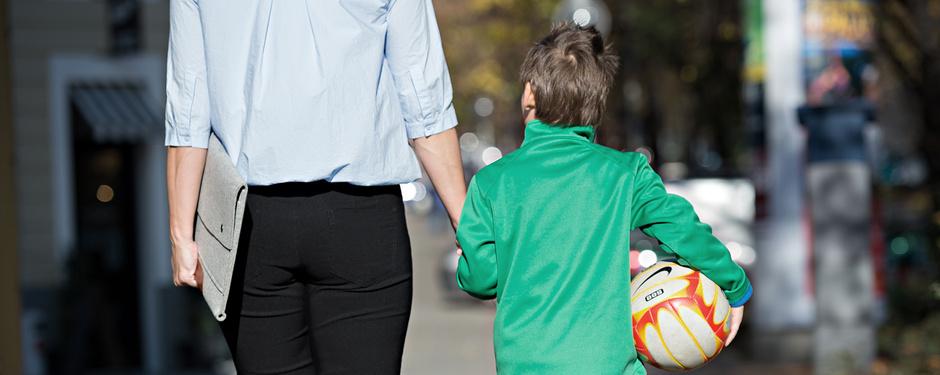 Vereinbarkeit von Familie und Beruf: Mitarbeiterin mit Kind an der Hand