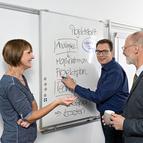 Drei Mitarbeiter am Whiteboard