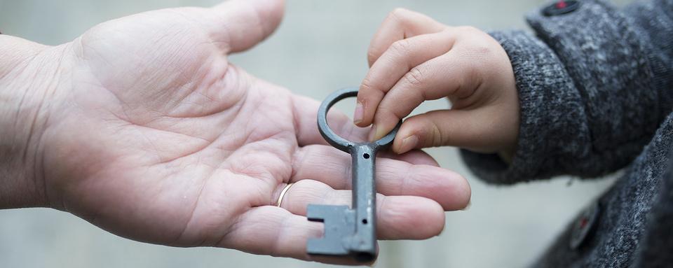 Bild, auf dem ein alter Schlüssel überreicht wird