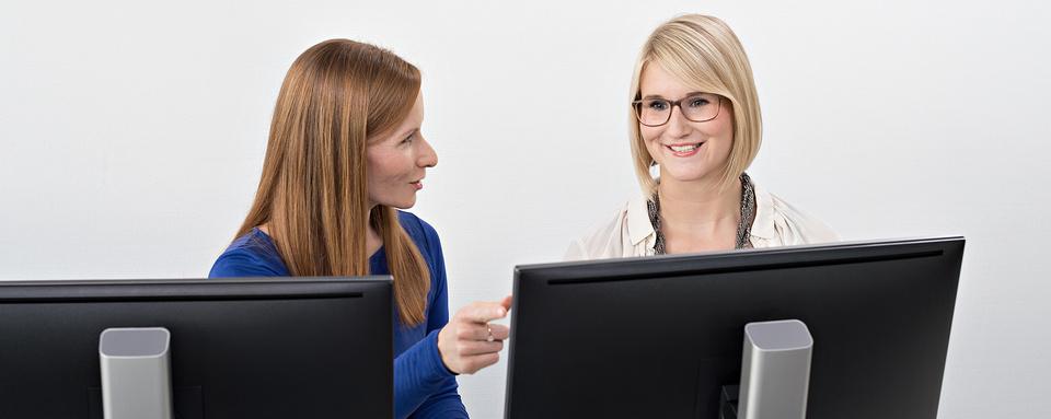 Ausbilderin und Auszubildende besprechen Ausbildungsinhalte am PC