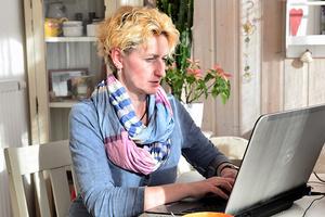 Frau sitzt zuhause im Arbeitszimmer und arbeitet