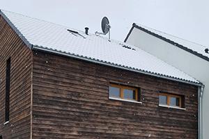 Ein mit Holz verkleidetes Strohballenhaus. Schnee liegt auf dem Dach.